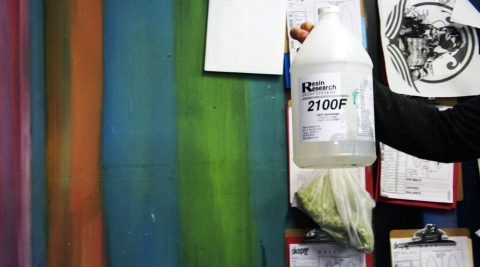 Chris Clark holding up a bottle of the epoxy chemicals used in his surf shop.