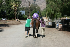Magic Horse Therapeutic Riding student rides alongside family members.