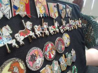 Hidden Mickeys are embedded in Disney pins, such as the one in the horse's tail.