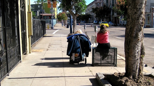 A homeless woman waits in front of the Salvation Army in Downtown San Diego.