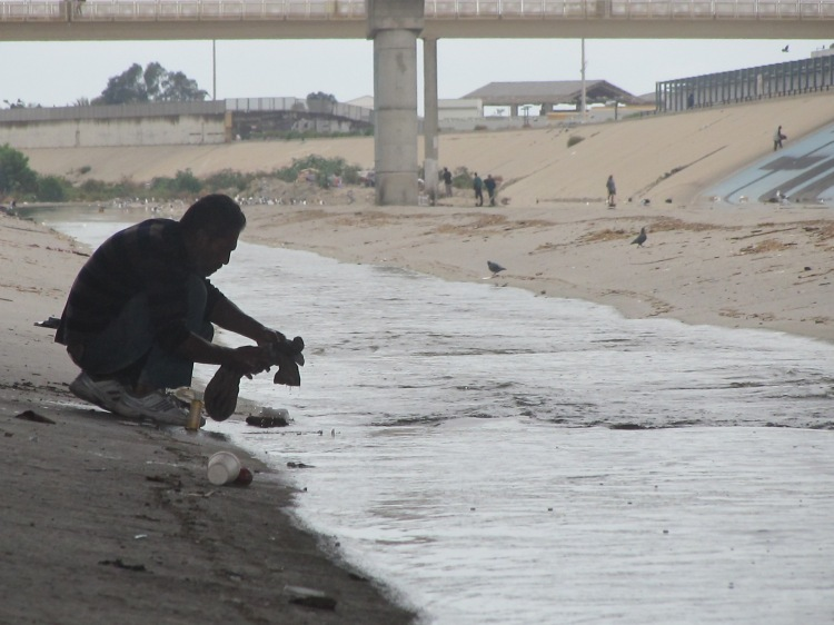 A resident of El Bordo washes his clothes in the Tijuana River.