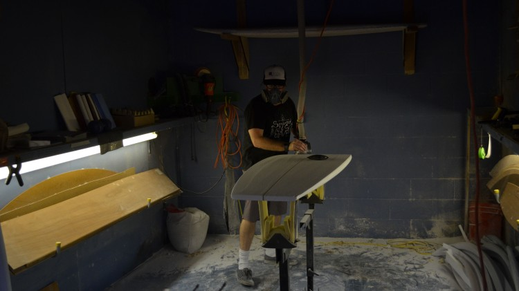 surfboard shaper working in studio