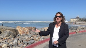 Kathy Weldon, program manager for the city of Encinitas, gestures to the riff raff the city built up around the parking lot at Moonlight Beach. Photo Casey Hands